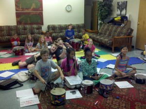 Students learning rhythm by playing drums